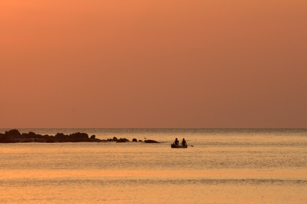 Two men in dugout canoe at sunset, Likoma Island