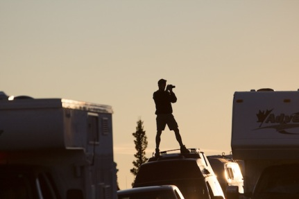 Some dude riding on top of a van trying to photograph a moose.