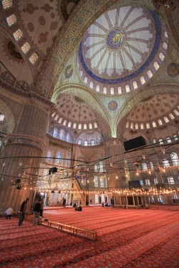 The 10mm lens greatly distorts the interior of the Blue Mosque. Lights are suspended from the ornate ceiling and worshipers take a place on the carpet for prayers.