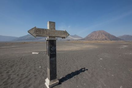 Road sign on the sand sea