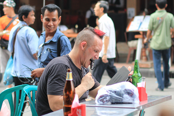 Tourist eating scorpion on Khao San Road