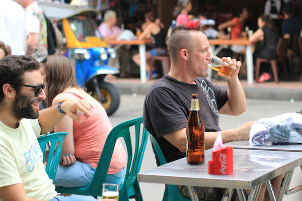 Tourist eating scorpion with beer