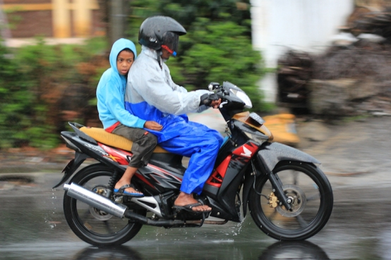 Boy on motorcycle in rain