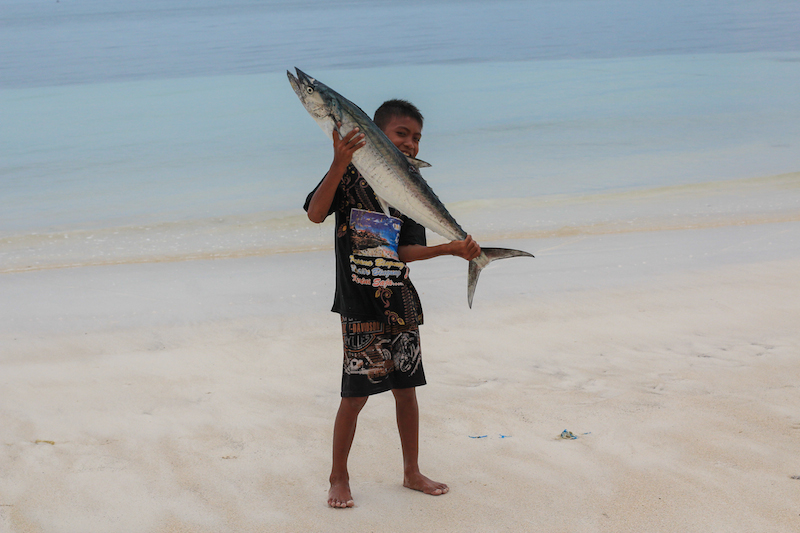 Bira beach boy with fish