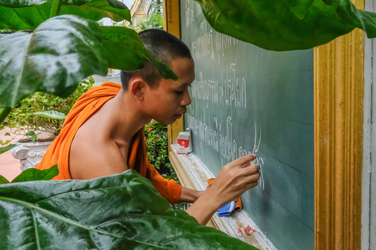 Monk writing on chalkboard